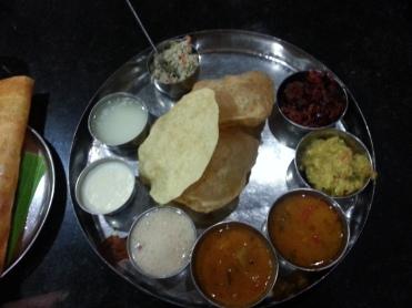 The complete Kannada meal: puris, papad, beetroot palya, puttu (ground rice+grated coconut), rasam, sambar, curd, whey and payasam (dessert)