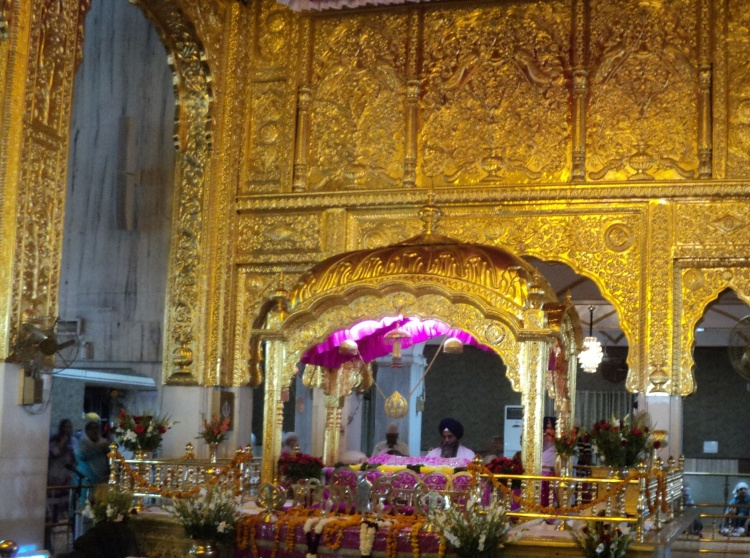At the centre of the gilded shrine, the Granthi reads the Sikh scripture